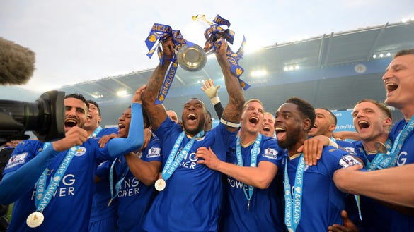 LEICESTER, ENGLAND - MAY 07: Captain Wes Morgan of Leicester City lifts the Premier League Trophy as players celebrate the season champions after the Barclays Premier League match between Leicester City and Everton at The King Power Stadium on May 7, 2016 in Leicester, United Kingdom. (Photo by Michael Regan/Getty Images) ORG XMIT: 569698369 ORIG FILE ID: 528946496