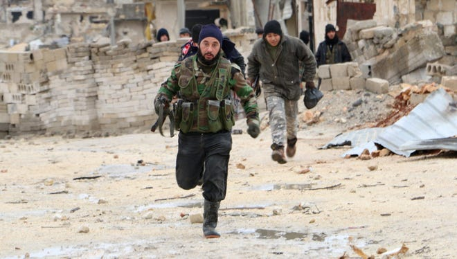 Opposition fighters run across the street in the al-Breij area northwest on the northern Syrian town of Aleppo Jan. 7, 2015.