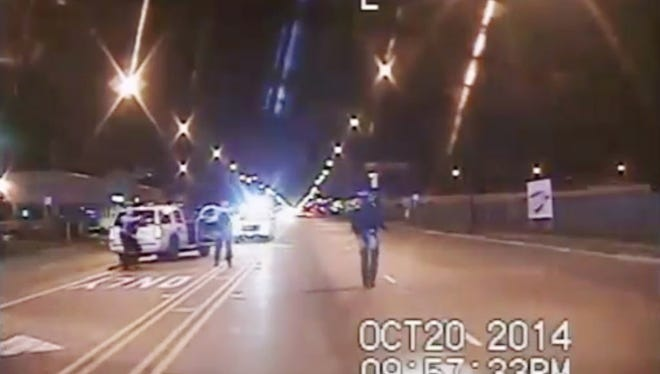 In this Oct. 20, 2014 frame from dash-cam video provided by the Chicago Police Department, Laquan McDonald, right, walks down the street moments before being shot by officer Jason Van Dyke in Chicago.