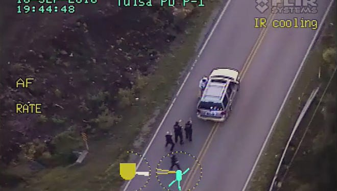 In this image made from a Friday, Sept. 16, 2016 police video, Terence Crutcher, top, is pursued by police officers as he walk to an SUV in Tulsa, Okla. Crutcher was taken to the hospital where he was pronounced dead after he was shot by the officer around Friday, police said.