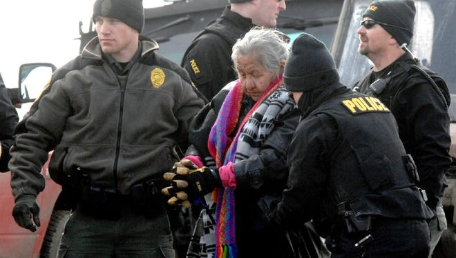 An elderly woman is escorted Thursday to a transport van after being arrested by law enforcement at the Oceti Sakowin camp as part of the final sweep of the Dakota Access pipeline protesters in Morton County, near Cannon Ball, N.D.