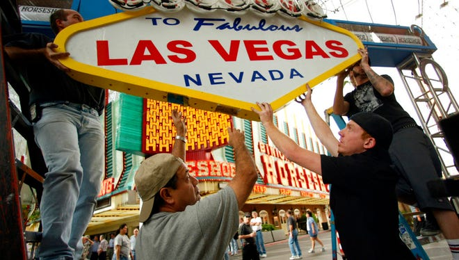 In this April 1, 2004, file photo, workers prepare the stage for a ribbon-cutting ceremony in front of Binion's Horseshoe Casino on Fremont Street in downtown Las Vegas. Forty neon signs that once drew visitors to some of Las Vegas' most iconic casino-hotels and other venues will shine again for the public starting Wednesday, Jan. 31, 2018, night at the Neon Museum.