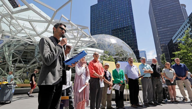 Shankar Narayan, legislative director of the ACLU of Washington, left, speaks at a news conference outside Amazon headquarters, Monday, June 18, 2018, in Seattle. Representatives of community-based organizations urged Amazon to stop selling its face surveillance system, Rekognition, to the government. They later delivered the petitions to Amazon.