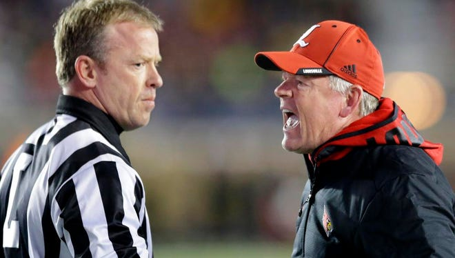 Louisville head coach Bobby Petrino, right, expresses his displeasure to a linesman after his team was called for interference on a Boston College fair catch during the first quarter of an NCAA college football game Saturday, Nov. 8, 2014, in Boston. (AP Photo/Stephan Savoia)