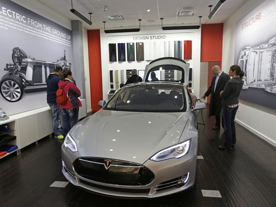 Customers check out a new Tesla all electric car on