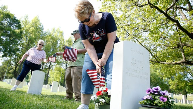 Jean Lathrop, of Gillett, Pennsylvania, plants a flag at a Woodlawn National Cemetery grave Friday in Elmira. She's inspired to attend the yearly flag planting, which prepares graves for the Memorial Day ceremony, so she can place flags at her sister, Gail Struble's, gravesite and other family members sites.
