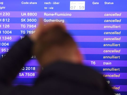 A file photo shows a passenger standing in front of a Frankfurt airport departure board.
