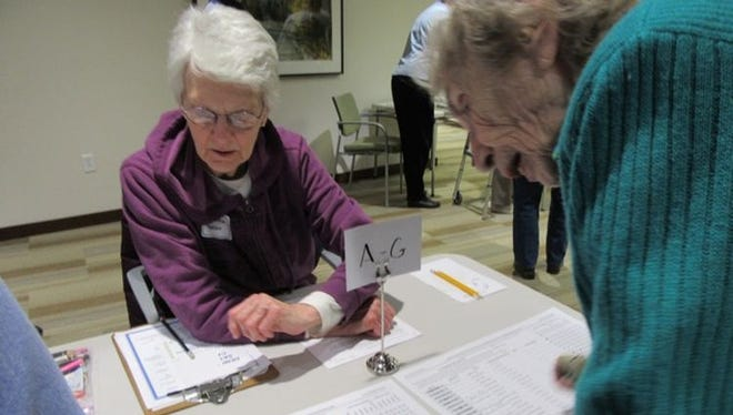 Participants sign in Monday at a satellite caucus site in Oaknoll Retirement Community in Iowa City.
