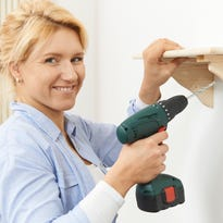 Photo illustration of a woman putting up a shelf with a cordless drill