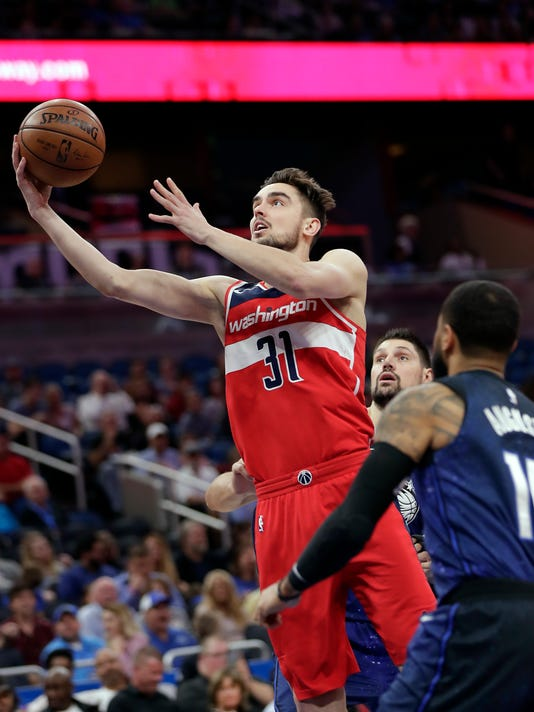 Washington Wizards' Tomas Satoransky (31) goes to the basket as he gets between Orlando Magic's Nikola Vucevic, back center, and D.J. Augustin (14) during the first half of an NBA basketball game, Wednesday, April 11, 2018, in Orlando, Fla. (AP Photo/John Raoux)
