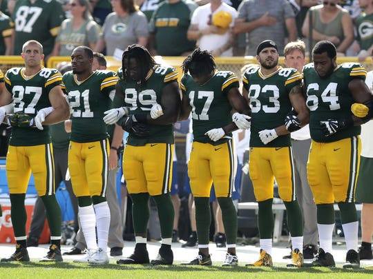 The Green Bay Packers lock arms during the national anthem on Sunday, September 24, 2017, at Lambeau Field in Green Bay, Wis.