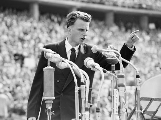 The Rev. Billy Graham speaks to more than 100,000 Berliners at the Olympic Stadium in Berlin, Germany, in 1954.   A counselor to presidents and the most widely heard Christian evangelist in history, Graham died in his native North Carolina Wednesday, February 21, 2018, at age 99.