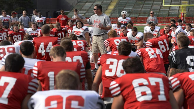 St. John's University head coach Gary Fasching talks to the players during a break in the action at practice Wednesday at Clemens Stadium.