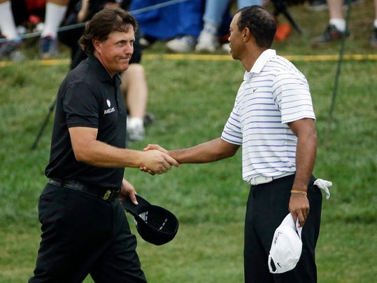 Phil Mickelson, left, shakes Tiger Wood's hand after the second round of the PGA Championship golf tournament at Valhalla Golf Club on Friday, Aug. 8, 2014, in Louisville, Ky. (AP Photo/David J. Phillip)