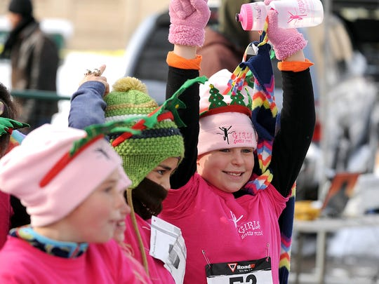 Madison DeQuasie raises her arms in victory after she finishes the Jingle Bell 5K in 2011 at the CSU Oval in Fort Collins.