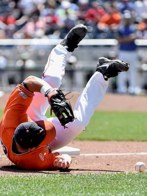Virginia third baseman Kenny Towns takes a tumble while trying to field the ball, hit for a single by Florida's Dalton Guthrie in the third inning of their College World Series  game Friday at TD Ameritrade Park in Omaha, Neb.