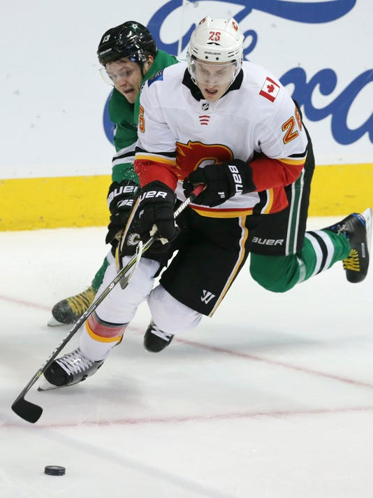 Calgary Flames center Freddie Hamilton (25) skates with the puck against Dallas Stars center Mattias Janmark (13) during the first period of an NHL hockey game in Dallas, Friday, Nov. 24, 2017. (AP Photo/LM Otero)