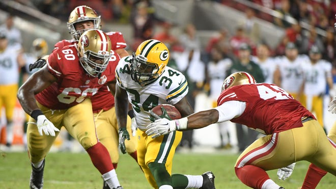 Green Bay Packers running back Brandon Burks runs past San Francisco 49ers defensive end B.J. McBryde (60) and linebacker Wynton McManis for a touchdown during the fourth quarter at Levi's Stadium.