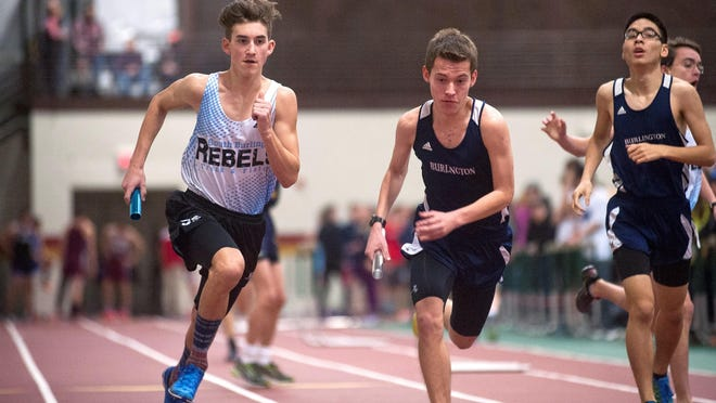 South Burlington's Finley Killeen, left, takes the handoff for the second leg next to Burlington's Carl Crawford in the Division I boys 4x800 meter relay during the Vermont indoor track state championships on Saturday at Norwich University.