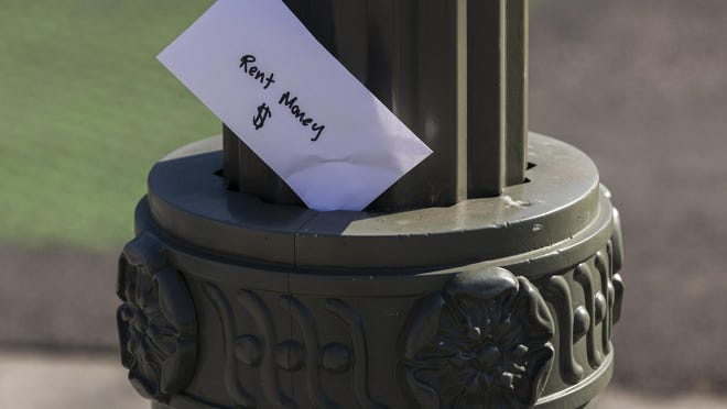 """A paper envelope written with the words """"Rent Money $"""" is left tucked in a lighting pole in the Boyle Heights east district of the city of Los Angeles on Wednesday, April 1, 2020. The Ottawa County Housing Commission and 58th District Court have asked federal and state lawmakers for an extension of funding programs designed to prevent evictions."""