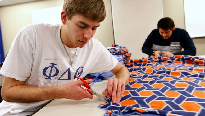 Drake junior Sean Buczek of Crystal Lake, Ill. (left), and junior Anthony Hernandez of Bakersfield, Calif., cut strips into a pair of fleeces Saturday, March 28, 2015, as members of the Phi Delta Theta fraternity make fleece tie blankets for ALS patients at the Olmstead Center at Drake University in Des Moines. The blankets will be donated in April to a local ALS support group, where they will be given to wheelchair-bound patients of the disease to keep warm.