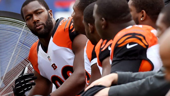 Cincinnati Bengals defensive end Michael Johnson (93) talks with other defensive players on the bench last season.