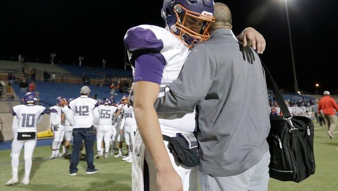 Eastlake head coach JJ Calderon talks to his quarterback Keith Tarango after their 59-26 loss to Lubbock Monterey in the area round championship game Friday at Grande Communications Stadium in Midland.