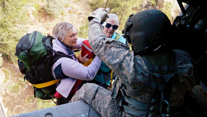 Two women are hoisted into a Blackhawk helicopter as they are rescued near Jamestown, Colo., on Tuesday.