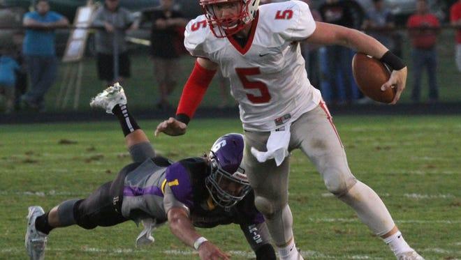 Shelby quarterback Brennan Armstrong stumbles over Lexington's Logan Pfizenmayer on Friday night.