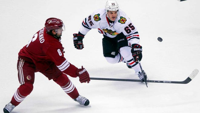 The Coyotes' David Schlemko (left) battles the Blackhawks' Andrew Shaw for a loose puck in the first period of a Feb. 7, 2014 game in Glendale.