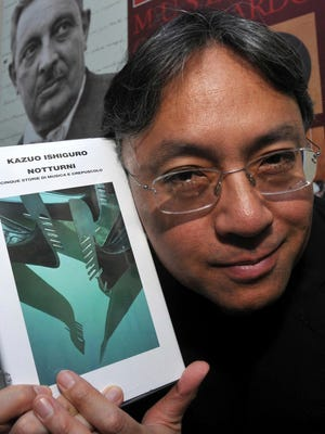 In this Aug 8, 2009, file photo, author Kazuo Ishiguro shows his book 'Nocturnals' before receiving the Giuseppe Tomasi di Lampedusa prize for literature, in Santa Margherita Belice, near Palermo, Sicily, southern Italy.