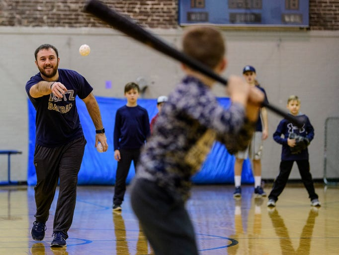 Coach Drew Johnston pitches a wiffle ball to a child