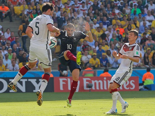France's Karim Benzema, center, kicks up dust as he is challenged by Germany's Mats Hummels, left, and Toni Kroos during the World Cup quarterfinal soccer match between Germany and France at the Maracana Stadium in Rio de Janeiro, Brazil, Friday, July 4, 2014. (AP Photo/David Vincent)