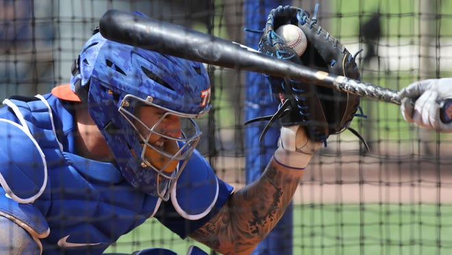 Mets catcher Tomas Nido gets grazed by a bat as he catches the ball pitched by Steven Matz during spring training.