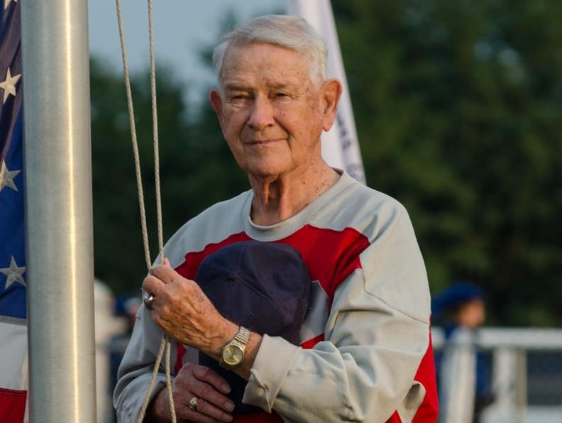 Don Jakeway raises the flag at Friday's Johnstown season opener, which he has been doing for more than 40 years.