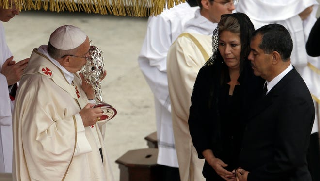 Pope Francis kisses the relic of Pope John Paul II she received from Floribeth Mora, second right, a Costa Rican woman whose inoperable brain aneurysm purportedly disappeared after she prayed to John Paul II, during a solemn ceremony in St. Peter's Square at the Vatican. Pope Francis has declared his two predecessors John XXIII and John Paul II saints in an unprecedented canonization ceremony made even more historic by the presence of retired Pope Benedict XVI.