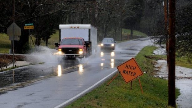 FILE - Drivers deal with high waters crossing Tipton Station Road during heavy rain in January 2015.
