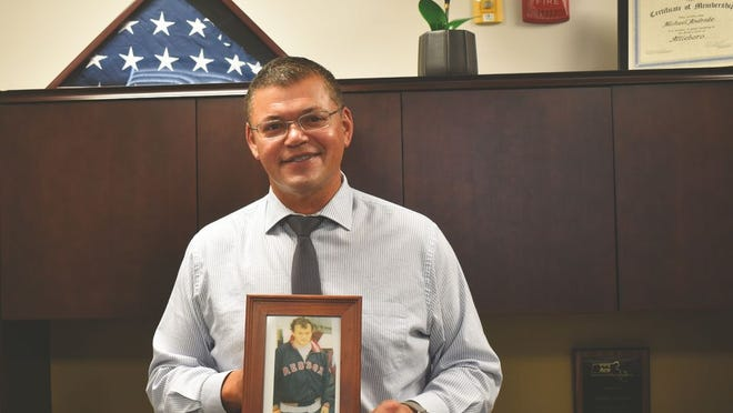 The ARC of Bristol County President and CEO Michael Andrade stands in front of an American flag made by ARC holding a photo of Michael, a former client who worked on that flag. The flag was sent to Afghanistan where it was flown and then sent back to the ARC as a souvenir.