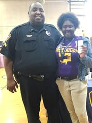 Jamilya Hills, a student at Paul Breaux Middle, talks with Lafayette Police Department Cpl. Jarvis Mayfield at the school's college and career day Thursday.