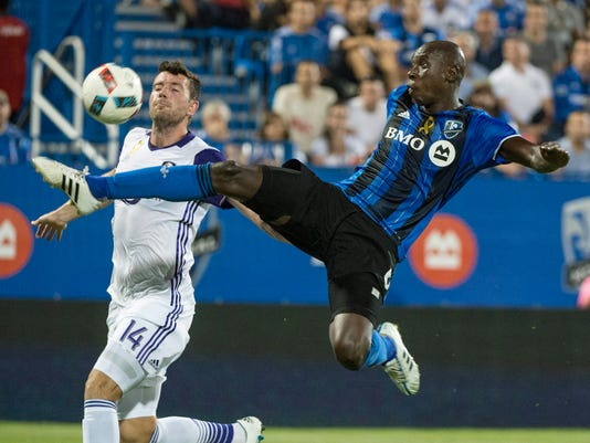 Montreal Impact defender Hassoun Camara kicks the ball away from Orlando City FC defender Luke Boden during the first half of an MLS soccer game Wednesday, Sept. 7, 2016 in Montreal. (Paul Chiasson/The Canadian Press via AP)