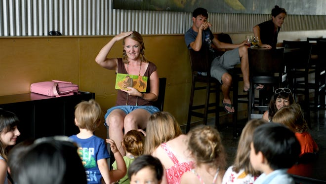 Corina Casanova reads a book to children as many of their parents enjoy a beer nearby during Afternoon Story Time at Archetype Brewing on Wednesday, June 21, 2017. Casanova is one of the owners of the new brewery which has made efforts to be family-friendly.