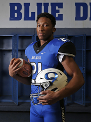 Jirehl Brock poses for a photo in the locker room at