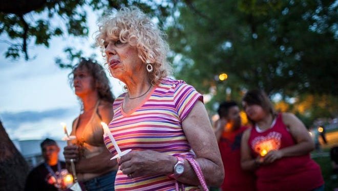 Denee Mallon, center, joins a candlelight vigil organized by Albuquerque Pride in Albuquerque, N.M., on Thursday. A U.S. Department of Health and Services review board ruled Friday in favor of Mallon, a 74-year-old Army veteran, whose request to have Medicare pay for her genital reconstruction was denied two years ago. The decision recognizes sex reassignment surgeries as a medically necessary and effective treatment for individuals who do not identify with their biological sex.