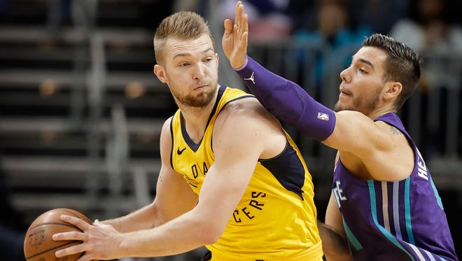Indiana Pacers' Domantas Sabonis, left, drives against Charlotte Hornets' Willy Hernangomez, right, during the first half of an NBA basketball game in Charlotte, N.C., Sunday, April 8, 2018.