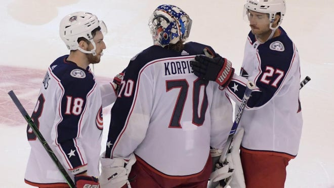 Pierre-Luc Dubois (18) and Ryan Murray console Joonas Korpisalo after Tuesday's five-overtime loss to the Lightning in which the Jackets goalie made an eye-popping 85 saves.