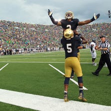 Aug 30, 2014; South Bend, IN, USA;  Notre Dame Fighting Irish quarterback Everett Golson (5) is congratulated by wide receiver Amir Carlisle (3) after scoring a touchdown during a game against the Rice Owls at Notre Dame Stadium. Mandatory Credit: Brian Spurlock-USA TODAY Sports