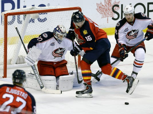 Columbus Blue Jackets goalie Curtis McElhinney (30) deflects a shot by Florida Panthers center Nick Bjugstad (27) in the first period of an NHL hockey game in Sunrise, Fla., Thursday, Jan. 29, 2015. (AP Photo/Alan Diaz)