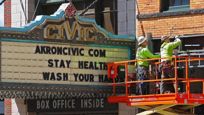Workers from Welty Building Company work alongside the Akron Civic Theatre's marquee, Thursday, April 2, 2020, in Akron, Ohio.