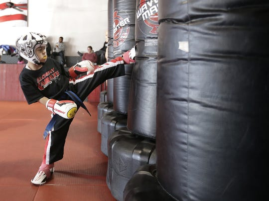 Five-year-old Christian Alvarado works the bags during a training session at Alchemy Karate Academy.