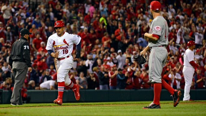 Cardinals center fielder Jon Jay scores on a sacrifice fly by second baseman Kolten Wong (not pictured) as Reds starting pitcher Mike Leake looks on during the eighth inning Sunday night at Busch Stadium.